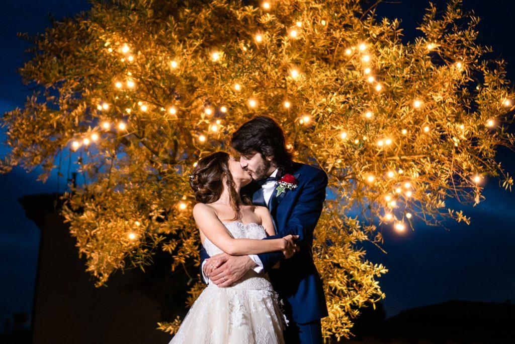 sposi abbracciati-sfondo albero di luci gialle e cielo azzurro
