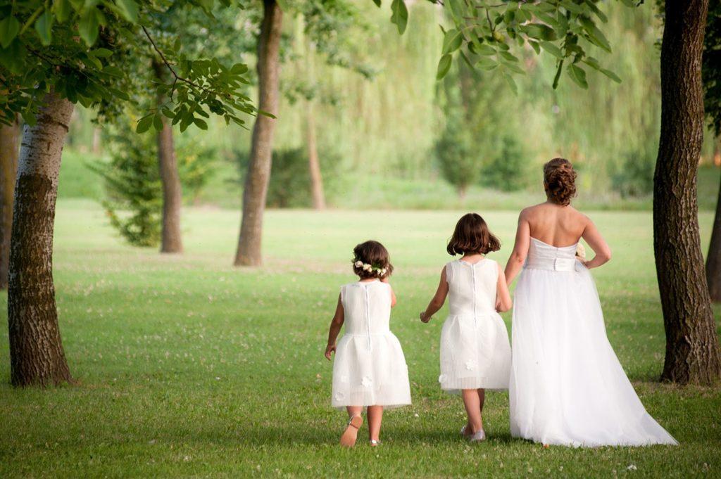 sposa cammina nel verde con le damigelle